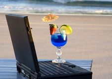 Down tools. Beach with laptop on a table with a blue cocktail on the laptop, with the beach in the background stock photo