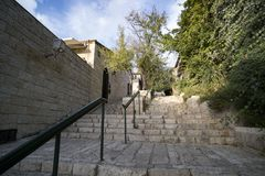 Down-top view of the vintage stone walls and stairs with modern handrails at a sunny summer day. Old city stairs surrounded by. Green trees and stone buildings stock photos