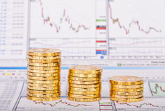 Down trend stacks of golden coins and financial chart as the bac Royalty Free Stock Image