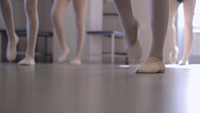 Down view of beautiful women marching limbering up in model school. Young fashionable females are changing feet going in place trying to hold balance and pose stock footage