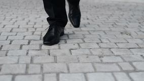 Down view on groom walking on pavement