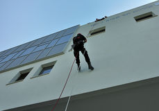 Down on the wall. Firefighter / rescue team member demonstrates sliding down from the top of a building with ropes on the wall. Took place in Tel-Aviv at the stock photo