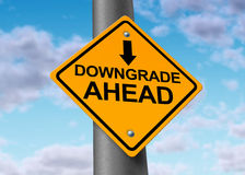 Downgrade of a company symbol. Downgrade symbol represented by a traffic sign warning that there will be bad news for a company that will result in a lower price Royalty Free Stock Photos