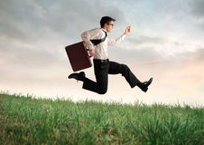 Downhill. Businessman running downhill on a green meadow Royalty Free Stock Image