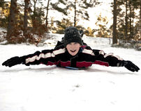 Downhill on belly. Young boy gliding on his belly in the snow Royalty Free Stock Photography