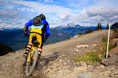 Downhill bike. A biker is going to a downhill ride in the rocky mountains Royalty Free Stock Image
