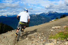 Downhill bike. A biker is going to a downhill ride in the rocky mountains Stock Photo