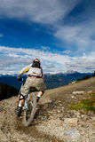 Downhill bike. A biker is going to a downhill ride in the rocky mountains Stock Photography