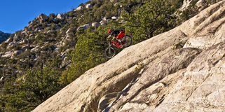 Downhill bike rider rides down Stock Images
