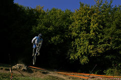 Downhill racer after jump. Downhill bike racer after jump with trees in the background royalty free stock photography