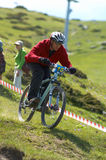 Downhill racer in red. Red racer on sky blue on extreme downhill race in mountain ski resort Stock Photo