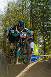 Downhill rider focused over rock obstacle Royalty Free Stock Photography