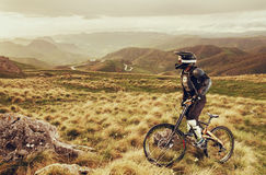 Downhill rider on a mountain bike in a mountain bike rides along the road in nature against the backdrop of the mountain Royalty Free Stock Photos