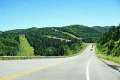 Downhill road with mountains and coniferous trees Stock Image
