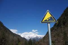 Downhill road sign with snow mountains Stock Images