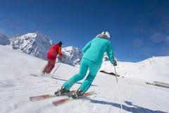 Downhill skiing - arrive in ski lodge. Alpine skiing on ski run by sunny weather Royalty Free Stock Image