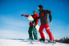 Downhill skiing, skiers on the top of slope. Downhill skiing, male and female skiers on the top of slope. Winter season active sport, extreme lifestyle Stock Image