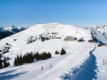 Downhill slope and apres ski mountain hut with restaurant terrace in Saalbach Hinterglemm Leogang winter resort, Tirol Stock Photos