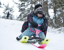 Downhill on a snow sledge. Two young boys going downhill on a modern snow sledge Royalty Free Stock Images