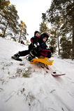 Downhill on a snow sledge. Two young boys going downhill on a snow sledge Stock Image