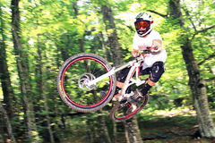 Downhiller durante um salto Imagens de Stock
