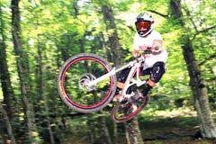 Downhiller durante un salto Imagenes de archivo