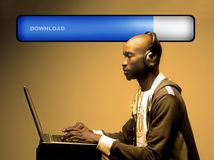 Download. A black boy with ear-phones doing a music download stock images