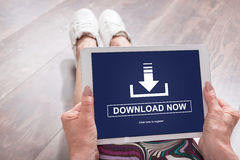 Download concept on a tablet. Woman sitting on the floor with a tablet showing download concept Stock Photography