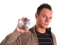 Download music. A handsome teenager holding a cd oder dvd. All isolated on white background Royalty Free Stock Photos