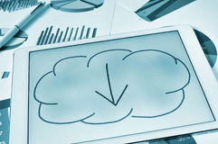 Downloading from the cloud. A drawing of a cloud with an arrow inside on the screen of a tablet, depicting the concept of download from the cloud storage Stock Photo