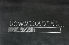 Downloading. Handwritten with white chalk on a blackboard and drawing download bar stock photo