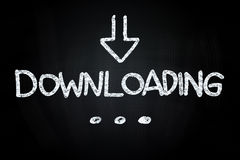 Downloading. Writting with Down Sign Arrow, drawn with Chalk on Blackboard Royalty Free Stock Image