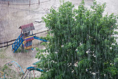 Downpour. Heavy rain against the tree and a children's playground Royalty Free Stock Image