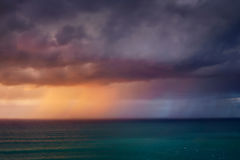 Downpour in the sea at sunset. Downpour in the sea at the sunset Stock Photo
