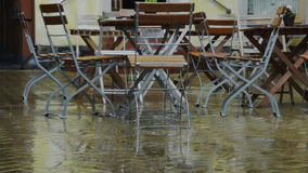 Downpour in small historic shopping area with flowerpots stock video footage