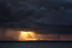 Downpour and sun rays on the sea. At sunset Royalty Free Stock Images