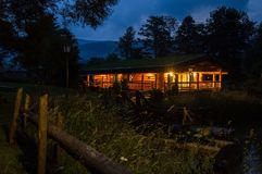 Downshifting lifestyle. Summer night. Wooden cabin hut in the Carpathian Mountains, illuminated by the warm light of lanterns