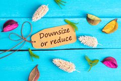 Downsize or reduce text on paper tag. With rope and color dried flowers around on blue wooden background stock images