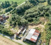 Downsized plant for the repair of machines with a scrap yard behind a forest with a wild dump, diagonally shot aerial photograph. Royalty Free Stock Photos