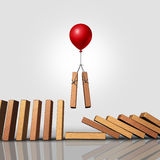 Downsizing. Business strategy as a balloon lifting up a pair of domino pieces allowing the gap to stop the falling dominoes as a corporate management symbol and Stock Photography