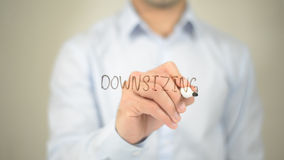 Downsizing , man writing on transparent screen royalty free stock image