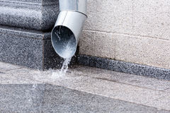 Downspout in heavy rain. Rain water flowing from a metal downspout during a heavy rain stock image