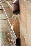 Downspout during the rain. In city royalty free stock images