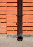 Downspout van de huisdakgoot met muurhouder zonder waterdrainage op de bestrating stock fotografie