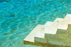 Downstairs in the sea. Concrete staircase that leads straight down into the clear turquoise blue sea Stock Photography
