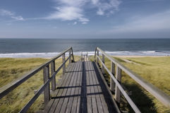 Downstairs to the ocean with soft blue sky. What a beautiful view to the ocean of the island of Sylt near Westerland in Germany Royalty Free Stock Photo