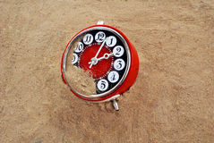 Downtime. Red a chijasy-alarm clock in a sandy ground Royalty Free Stock Photo