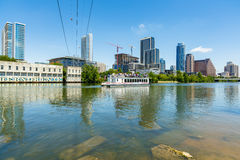 Downtown Austin Skyline. Austin, TX USA - April 14, 2016: Skyline view of  the downtown district along the Colorado River with a tour boat cruising by Royalty Free Stock Photos