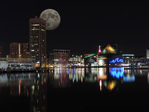 Downtown Baltimore Maryland Night Skyline Moon. A reflection of the skyline of downtown Baltimore, Maryland in the water of the Inner Harbor at night with the Stock Photo