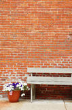 Downtown Bench on the Sidewalk. Small town bench in front of old brick wall next to flower pot of petunias and American flag Royalty Free Stock Photo